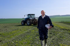 Smiling farmer holding lunchbox in field with tractor in background Royalty Free Stock Image