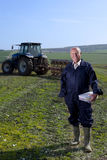 Smiling farmer holding lunchbox in field with tractor and plough in background Royalty Free Stock Image