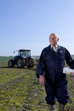 Smiling farmer holding lunchbox in field with tractor and plough in background Royalty Free Stock Images