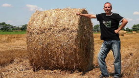 Smiling Farmer Leaning on Hay Bale In Agriculture Field. Smiling farmer posing in a stubble field next to a fresh round bale of hay. HD1080p stock footage