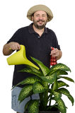 Smiling farmer likes to care flowers. Bearded smiling farmer likes to care flowers Stock Photos
