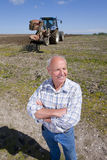 Smiling farmer standing with arms crossed in field with tractor and plough in background Stock Photos