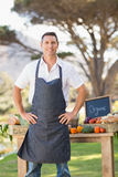 Smiling farmer standing with hands on hips Stock Photo