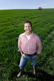 Smiling farmer standing with hands in pockets in young wheat field Royalty Free Stock Photo