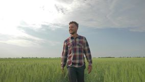 Smiling farmer waves his hand and shows an approval sign while walking through barley field on background of blue sky. Smiling farmer waves his hand and shows an stock video footage