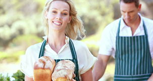 Smiling farmer woman holding breads. Portrait of a smiling farmer woman holding breads stock footage