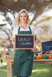 Smiling farmer woman holding a locally grown sign Stock Photos