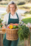 Smiling farmer woman holding a vegetable basket Stock Photo