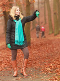 Smiling fashion blonde woman in jacket in park. Royalty Free Stock Image