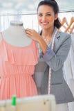 Smiling fashion designer adjusting dress stock images