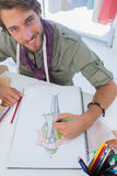 Smiling fashion designer drawing a coat Royalty Free Stock Photo