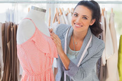 Smiling fashion designer fixing dress on a mannequin Stock Photography