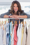 Smiling fashion designer leaning on clothes Royalty Free Stock Photos