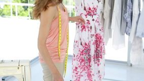 Smiling fashion designer looking at camera touching dress on mannequin stock video footage