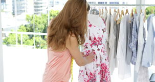 Smiling fashion designer looking at camera touching dress on mannequin stock footage