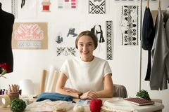 Smiling attractive fashion designer sitting at workplace looking. Smiling fashion designer looking at camera at workplace, dressmaker, needlewoman or tailor shop Royalty Free Stock Images