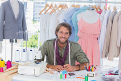 Smiling fashion designer sitting behind a desk Stock Photo