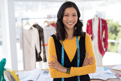 Smiling fashion designer standing with arms crossed in office. Portrait of smiling fashion designer standing with arms crossed in office royalty free stock photography