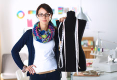 Smiling fashion designer standing near mannequin in office Royalty Free Stock Photo