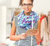 Smiling fashion designer standing near mannequin in office royalty free stock images