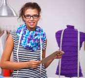 Smiling fashion designer standing near mannequin in office stock image