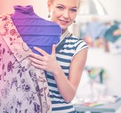Smiling fashion designer standing near mannequin in office stock photos