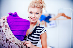 Smiling fashion designer woman standing near mannequin in office Stock Photos