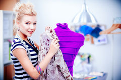 Smiling fashion designer woman standing near mannequin in office Stock Photo