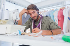 Smiling fashion designer working at his desk Stock Photo