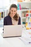 Smiling fashion designer working on laptop Royalty Free Stock Image
