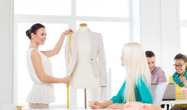 Smiling fashion designers working in office. Startup, education, fashion and office concept - smiling designers drawing sketches and measuring jacket on Royalty Free Stock Photography