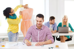 Smiling fashion designers working in office Stock Photo