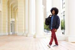 Smiling fashion guy walking outside with travel bag Royalty Free Stock Photo