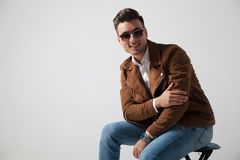 Smiling fashion man sitting and holds his elbow Stock Image