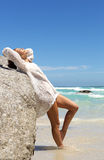 Smiling fashion model leaning on rock at the beach Stock Photos