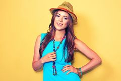 Smiling fashion model posing against yellow background. Woman portrait Stock Photos