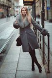 Smiling fashion model at the tram stop. Urban lifestyle Royalty Free Stock Photos
