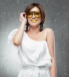 Smiling Fashion model. White dress on vintage gray Royalty Free Stock Photography