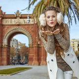 Smiling fashion-monger in Barcelona, Spain blowing air kiss Royalty Free Stock Photo