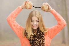 Smiling fashion woman in park holding earmuffs. Stock Photography