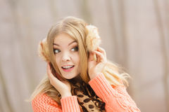 Smiling fashion woman in sweater and earmuffs. Stock Image