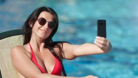 Smiling fashion woman in trendy sunglasses taking selfie using smartphone at sea water background. Medium close-up. Travel happy girl making photo on mobile stock footage