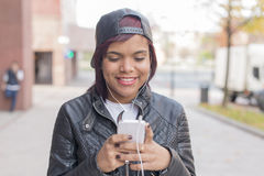 Smiling fashion young woman with headphones listening to music and walking in the street. Royalty Free Stock Photo