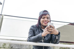 Smiling fashion young woman using smart phone in the street. Royalty Free Stock Images