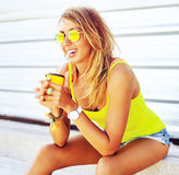 Smiling fashionable blonde drinking coffee outdoors Stock Photo