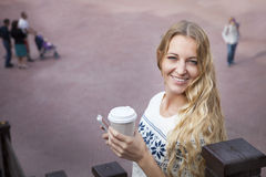 Smiling fashionable blonde woman holding coffee outdoors Royalty Free Stock Image