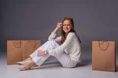 smiling fashionable girl in white clothes with shopping bags royalty free stock photography