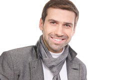 Smiling fashionable man wearing a scarf and gray clothes. Young fashionable man wearing a scarf and gray clothes isolated over a white background Stock Images