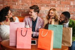 Smiling fashionable multiethnic young people with shopping bags. Drinking coffee royalty free stock photos