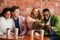 Smiling fashionable multiethnic young people using smartphone while. Drinking coffee stock photo